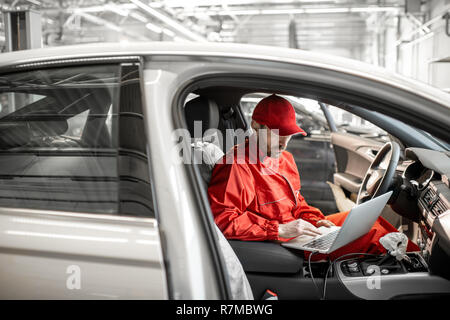 Auto mechanic in red uniform diagnosing car with computer sitting on the driver seat at the car service - Stock Photo