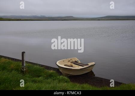 Icelandic landscape with a creme-white boat at lake Svinavatn. A rainy day with a cloudy sky. - Stock Photo