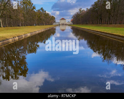 Nymphenburg castle, Munich, Germany, view along the canal , nice clouds in the sky, reflections in the water. - Stock Photo