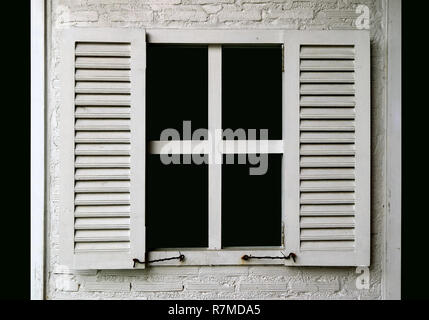 White colored wooden window on white painted brick wall - Stock Photo