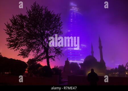 Azerbaijan, Baku, Alley of Martyrs, one of the illuminated glass flame towers glows at night behind the Turkish Mosque, also known as the Mosque of the Martyrs - Stock Photo
