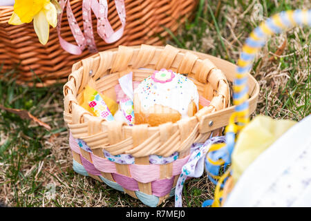 Cute pink Kulich Russian Orthodox Easter blessing wicker straw basket, on grass ground outside at church, many - Stock Photo
