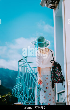 Young woman wearing summer clothes and straw hat going up stairs on sunny day. Vacation holidays in Europe - Stock Photo