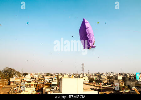 fire kite flying over clear blue sky during traditional hindu kite festival in indian city - Stock Photo