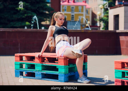 Fitness sporty girl wearing fashion sportswear over street wall, outdoor sports, urban style. Teen model in swag clothes posing outside - Stock Photo