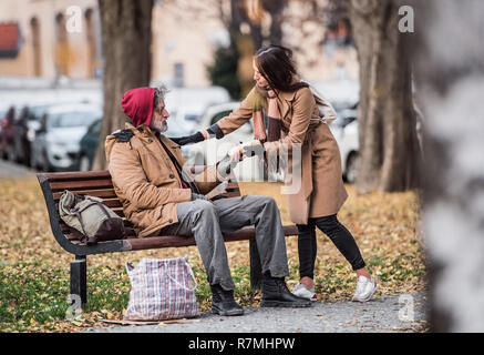 Young woman giving food to homeless beggar man sitting on a bench in city. - Stock Photo