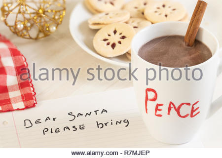 A note to Santa Clause, a cup of hot cocoa with a cinnamon stick, linzer cookies on a plate, a red and white check napkin, and a gold/pearl ornament - Stock Photo