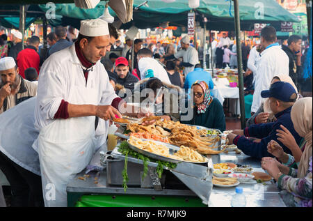 Marrakech street food - tourists and locals eating in the evening at a food stall in Djemaa el Fna square, Marrakech medina, Morocco Africa - Stock Photo