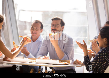 Businessman enjoying pizza with friendly colleagues during break - Stock Photo