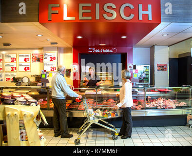 Senior couple shopping at the meat counter in the supermarket, Germany - Stock Photo