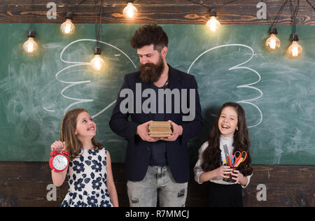 Favourite teacher concept. Man with beard and schoolgirls with school attributes. Teacher and girls pupils in classroom, chalkboard on background. Children and teacher with drawn by chalk wings. - Stock Photo
