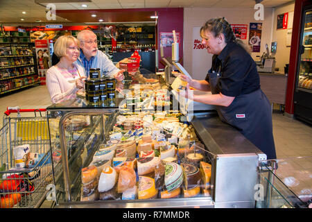 Shop assistant serving a senior couple at the cheese counter, shopping in a supermarket, Germany - Stock Photo