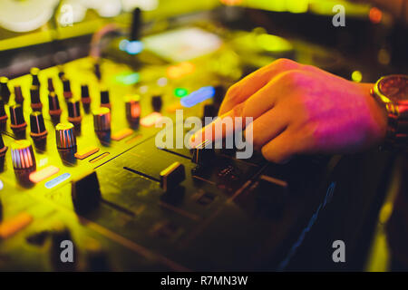 DJ mixing tracks on a mixer in a nightclub. - Stock Photo