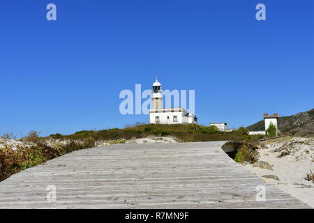 Beach with boardwalk and old abandoned lighthouse on a hill. Sunny day, blue sky. Galicia, Spain. - Stock Photo