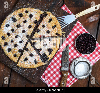 baked round black currant cake cut into pieces and sprinkled with powdered sugar on a brown wooden board - Stock Photo