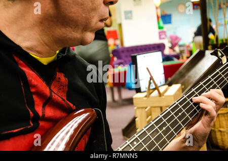 Closeup of photo of electric bass guitar player playing with hands - Stock Photo