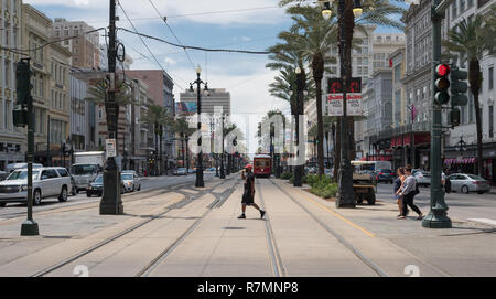 Male walking across the tram lines, Canal Street, New Orleans, Louisiana - Stock Photo
