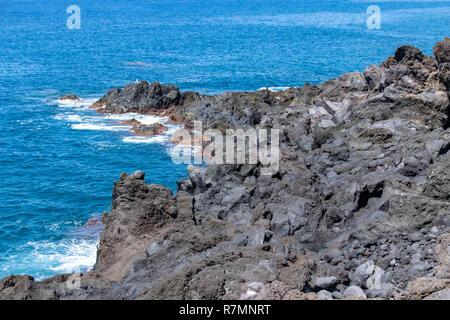 Atlantic ocean waves crashing over volcanic lava rocks on La Palma Island, Canary Islands, Spain - Stock Photo