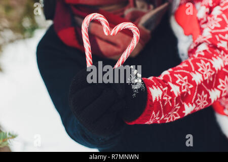 Lollipop stick in hand in mitten snow background christmas sweets concept. andies in heart shape. Candy in hand with a mitten on a background of snow. - Stock Photo