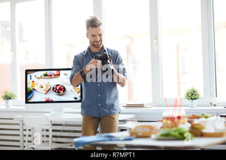 Portrait of successful photographer taking pictures of table with food while working in photo studio, copy space - Stock Photo