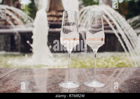 photograph of two glasses with champagne on the background of a fountain. beautiful color correction. - Stock Photo