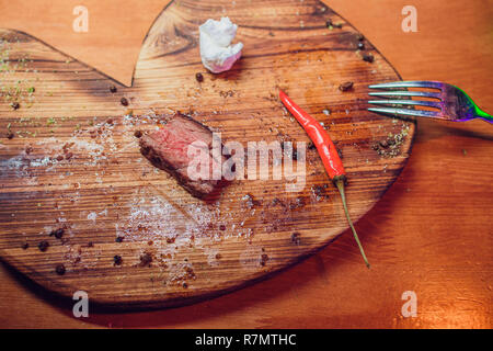 Sliced medium rare grilled Beef steak Ribeye with salt and pepper on meat cutting board on dark wooden background - Stock Photo