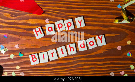 Happy Birthday Lettering with party decoration on wooden background, concept image, top view - Stock Photo
