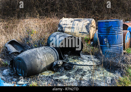 Barrels of toxic waste in nature, pollution of the environment. - Stock Photo