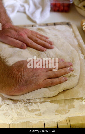 Close up of a man's hands kneading dough on a cutting board to make fresh bread - Stock Photo