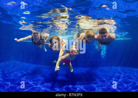 Happy family in swimming pool. Smiling mother, children and grandparents swim, dive in pool with fun - jump deep down underwater. Healthy lifestyle - Stock Photo