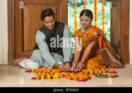 Happy maharashtrian couple in traditional dress sitting on the floor near entrance with flower decorations and pooja plate holding a diya. - Stock Photo