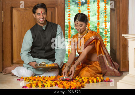 Happy maharashtrian couple in traditional dress sitting on the floor near entrance with flower decorations holding a diya and pooja plate. - Stock Photo