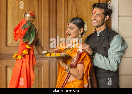 Happy maharashtrian couple in traditional dress celebrating gudi padwa festival holding a pooja plate. - Stock Photo