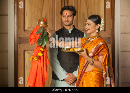 Maharashtrian couple in traditional dress celebrating gudi padwa festival holding a pooja plate. - Stock Photo