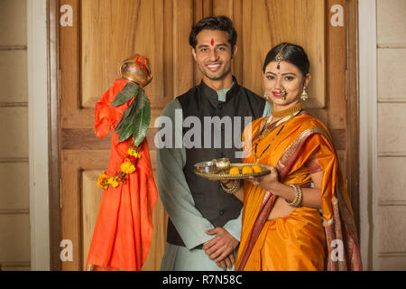 Happy maharashtrian couple in traditional dress celebrating gudi padwa festival holding a pooja plate and posing. - Stock Photo
