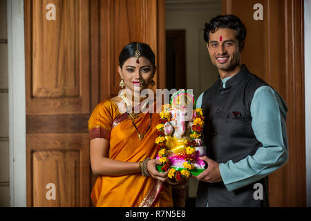 Maharashtrian couple in traditional dress celebrating ganapati festival holding a small statue of lord ganesha together. - Stock Photo