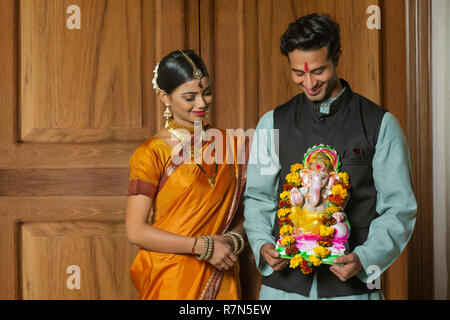 Maharashtrian couple in traditional dress celebrating ganapati festival holding a small statue of lord ganesha and looking at it. - Stock Photo