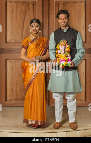 Portrait of happy maharashtrian couple in traditional dress celebrating ganapati festival holding a small statue of lord ganesha. - Stock Photo
