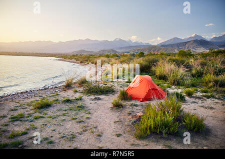 Orange tent on the shore of Issyk Kul mountain lake in Kyrgyzstan - Stock Photo