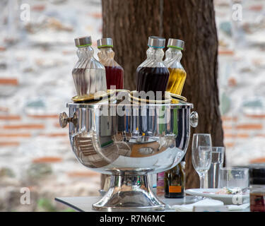 Cooling bottles with alcohol on the table set for dinner. The cooler reflects tables and chairs. Greece - Stock Photo