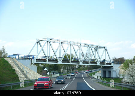 A steel railway bridge over a busy road for passenger cars. - Stock Photo