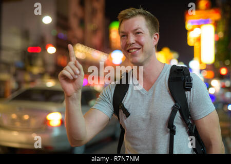 Young happy tourist man backpacker calling taxi in Chinatown at night - Stock Photo