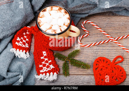 Cup of hot cocoa or chocolate with red scarf, handmade scarf and Christmas candy cane on wooden table, copy space. Christmas planning concept. - Stock Photo
