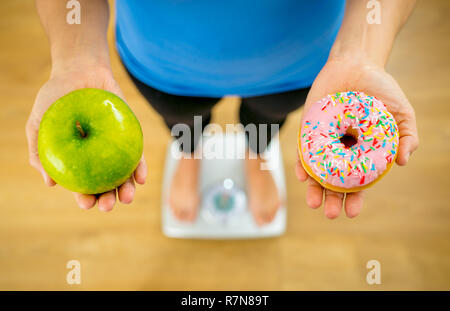 Close up of woman on scale holding on hands apple and doughnut making choice between healthy unhealthy food dessert while measuring body weight in Nut - Stock Photo