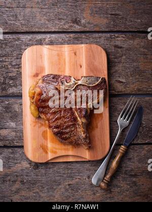 Grilled T-bone steak on wooden board - Stock Photo
