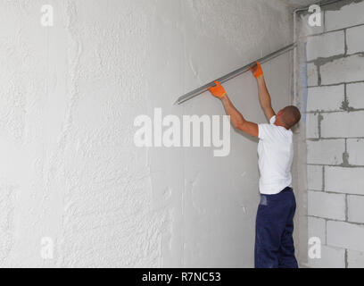 KYIV, UKRAINE - December 28, 2018: Worker plastering house walls,  finishing walls.  Wall screeding. Plastering walls techniques. - Stock Photo
