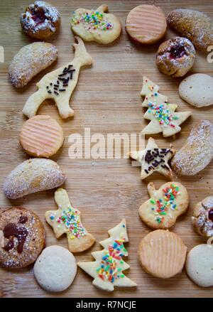 Selection of traditional German Christmas cookies on a rustic wooden board, butter cookies, anis biscuits, hazelnut cookies, cookies with jam filling - Stock Photo
