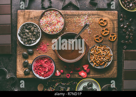 Homemade chocolate bars making. Various toppings and flavorings ingredients in bowls with melted chocolate on dark rustic kitchen table background, to - Stock Photo