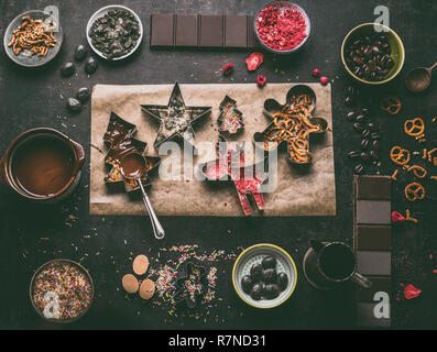 Homemade Christmas chocolate bars making. Christmas cutters with various toppings and flavorings. Melted chocolate in bowl with spoon on dark rustic k - Stock Photo