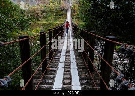 Woman walking on a wooden suspension bridge, Wakayama, Japan - Stock Photo